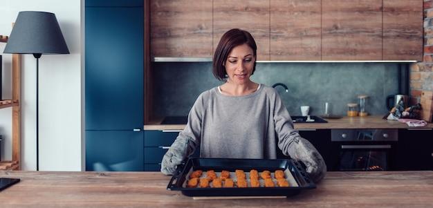 Femme tenant un plateau avec des pépites de poulet