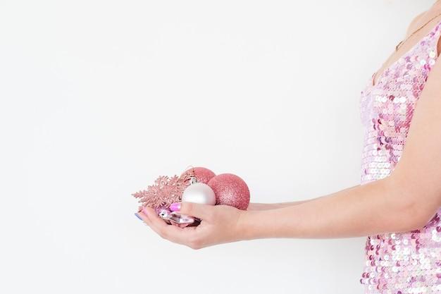 Femme tenant une poignée de boules scintillantes or rose sur blanc