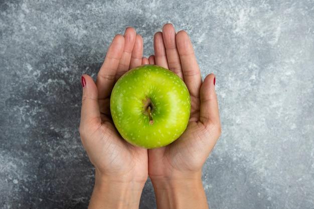 Femme tenant la pomme à deux mains sur le marbre.