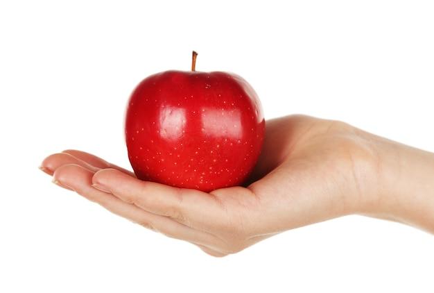 Femme tenant une pomme rouge, isolée sur un mur blanc