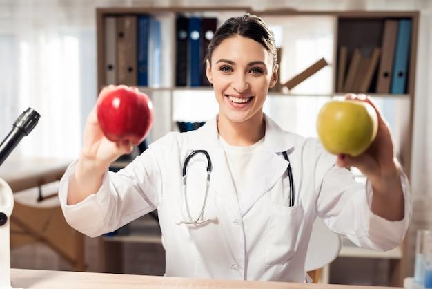 Femme tenant des pommes jaunes et rouges.