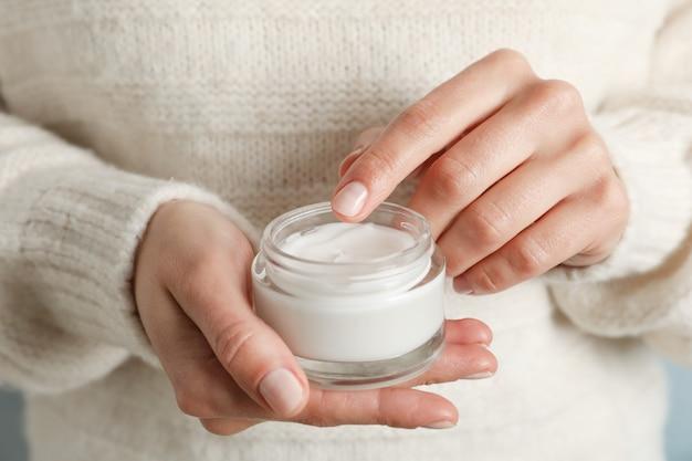 Femme tenant le pot de crème hydratante, gros plan. cosmétique d'hiver. espace pour le texte