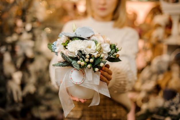 Femme tenant un pot de fleur avec des fleurs blanches décorées avec des feuilles vertes et des branches de sapin