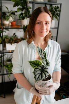 Femme tenant un pot de fleurs