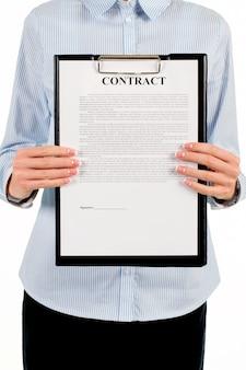 Femme tenant le presse-papiers avec contrat. femme d'affaires montrant le contrat sur le presse-papiers. veuillez lire ce document jusqu'au bout. nos conditions sont énoncées ici.