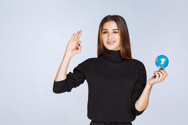 Femme tenant et promouvant un mini globe.
