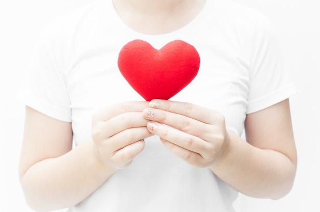 Femme tenant et protégeant une forme de coeur rouge sur fond blanc gros plan, symbole de l'amour ou datant de la saint-valentin