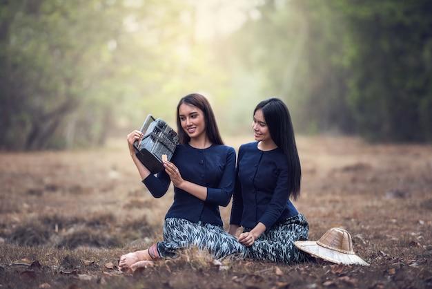 Femme tenant une radio dans un champ d'herbe