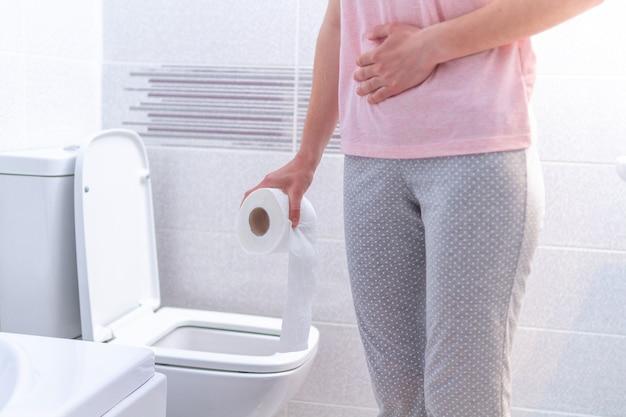 Femme tenant un rouleau de papier et souffrant de diarrhée, de constipation et de cystite aux toilettes. soins de santé
