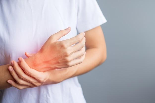 Femme tenant sa douleur au poignet parce qu'elle utilise un smartphone ou un ordinateur depuis longtemps. concept de ténosynovite de de quervain, symptôme d'intersection, syndrome du canal carpien ou syndrome de bureau