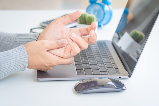 Femme tenant sa main de douleur de l'utilisation de l'ordinateur depuis longtemps