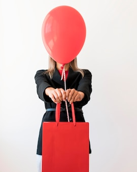 Femme tenant sac et ballon rouge couvrant son visage