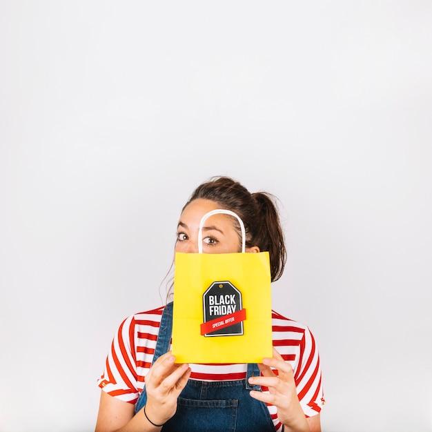 Femme tenant un sac jaune avec étiquette noir vendredi