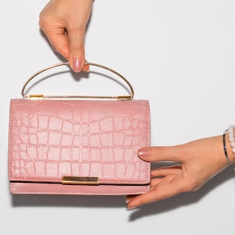 Femme tenant un sac à main en cuir rose