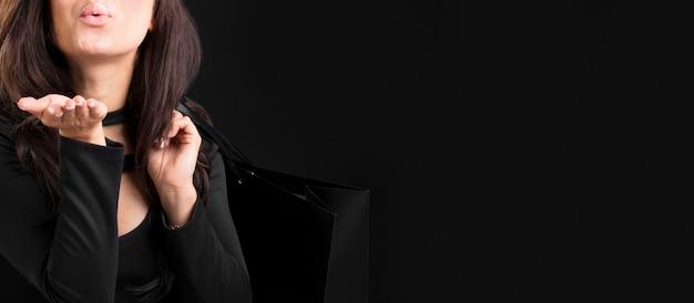 Femme tenant un sac à provisions noir et soufflant un baiser