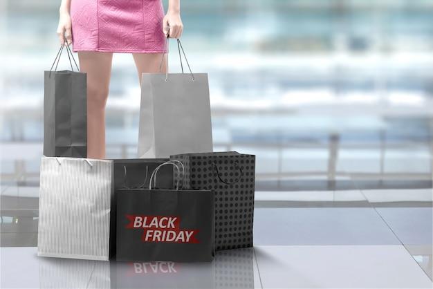 Femme tenant un sac à provisions avec une pile d'un sac à provisions avec texte du vendredi noir