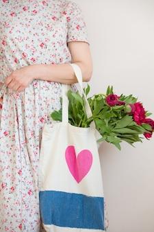 Femme tenant un sac en textile avec un beau bouquet de fleurs de pivoines rouges