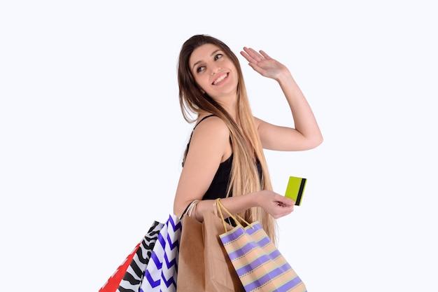 Femme tenant des sacs à provisions et carte de crédit.