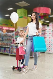 Femme tenant des sacs à provisions, fille à cheval sur scooter en centre commercial.