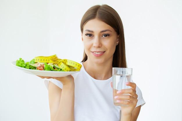 Femme tenant une salade diététique et un verre d'eau
