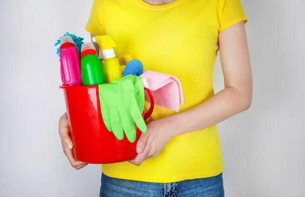 Femme tenant un seau avec des produits de nettoyage
