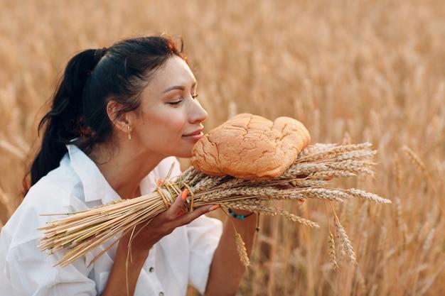 Femme tenant et sentant le pain de blé fait maison et la gerbe d'oreilles dans les mains dans le champ de blé au coucher du soleil.