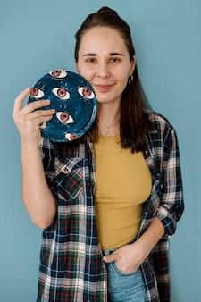 Femme tenant ses créations de poterie