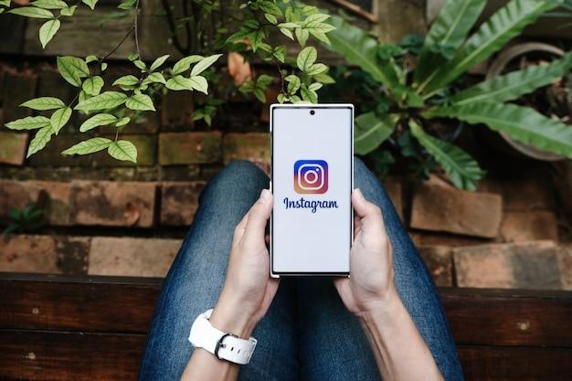 Une femme tenant un smartphone avec une application instagram à l'écran. instagram est une application de partage de photos pour smartphones.
