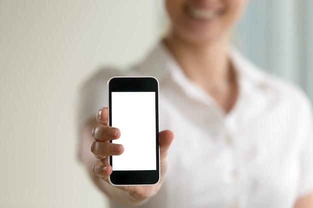 Femme tenant un smartphone, écran de maquette pour annonces mobiles, espace copie