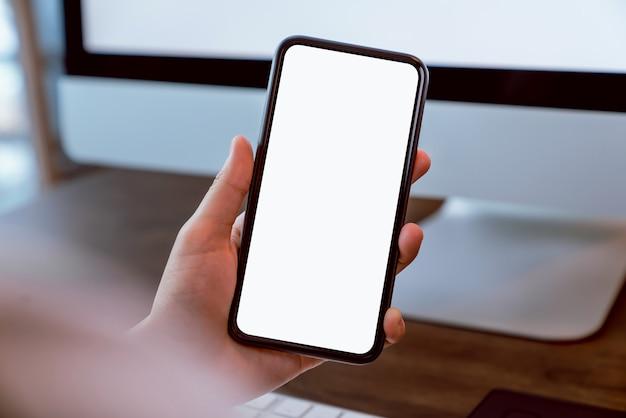 Femme tenant le smartphone de l'écran vide et de l'ordinateur sur le bureau de la table. prenez votre écran pour mettre de la publicité.