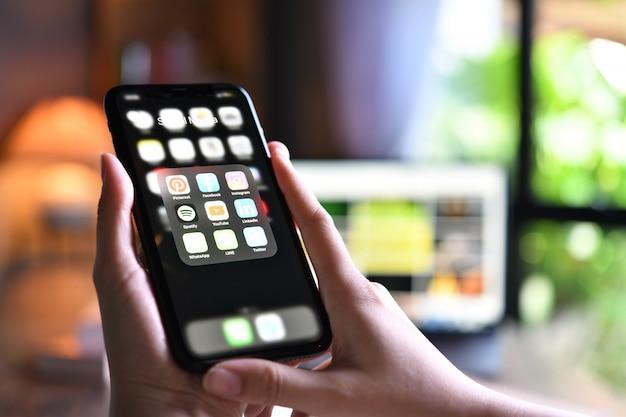 Femme tenant un smartphone avec des icônes de médias sociaux sur l'écran à la maison