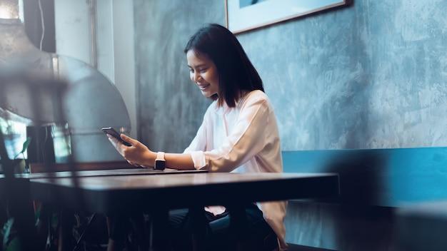 Femme tenant un smartphone, maquette d'écran vide. en utilisant un téléphone portable au café.