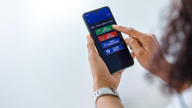 Femme tenant des smartphones et utilisant le toucher du doigt sur l'écran et sélectionnant les boutons de l'application d'achat et de vente pour le commerce d'argent numérique en bitcoin ou en crypto-monnaie avec espace de copie