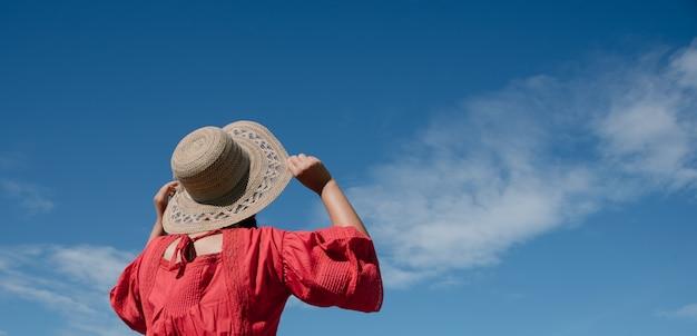 Femme tenant son chapeau tout en regardant vers le ciel