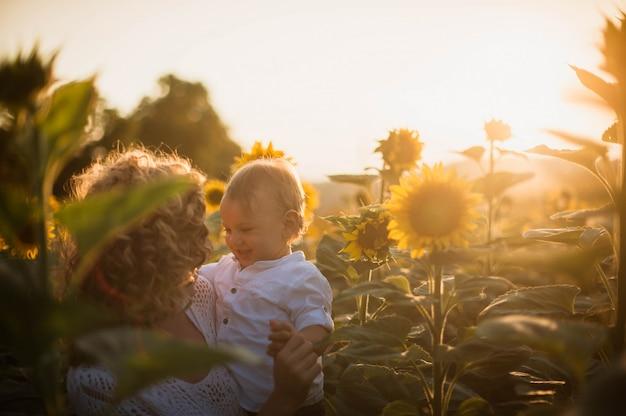 Femme tenant son fils au milieu d'un champ de tournesols