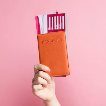 Femme tenant son passeport et ses billets d'avion