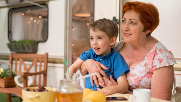 Femme tenant son petit-fils à côté d'une caravane