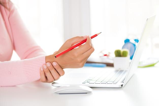 Femme tenant son poignet de douleur en utilisant un ordinateur. syndrome de bureau