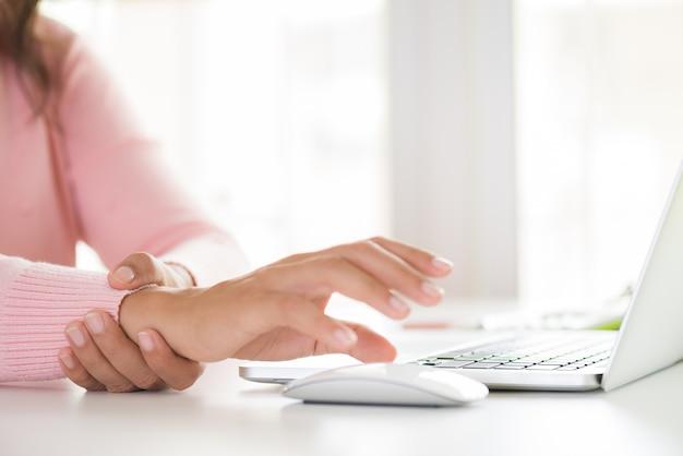 Femme tenant son poignet de douleur en utilisant un ordinateur. syndrome de bureau.