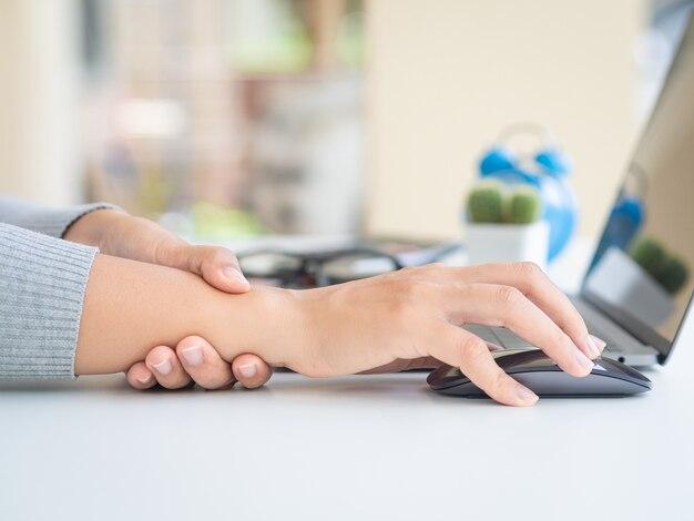 Femme tenant son poignet de douleur de l'utilisation de l'ordinateur depuis longtemps.