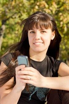 Femme tenant son téléphone portable assis dans un parc et souriant.