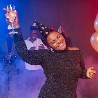 Femme tenant son verre de champagne et dansant