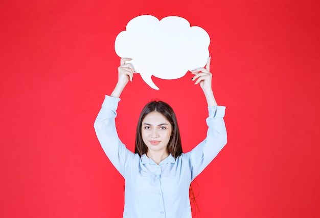 Femme tenant un tableau d'informations en forme de nuage.