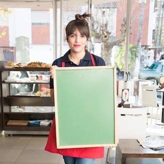 Femme tenant un tableau de menu vert vierge dans le café