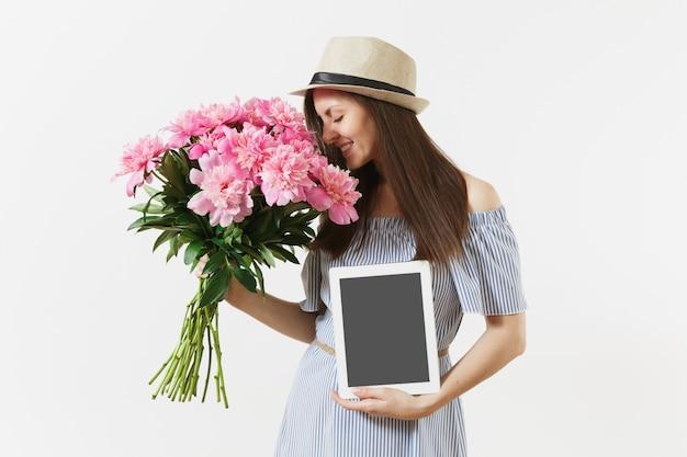 Femme tenant une tablette avec un écran vide pour copier l'espace, bouquet de belles fleurs de pivoines roses isolées sur fond blanc. concept de magasinage en ligne de livraison d'entreprise. espace publicitaire
