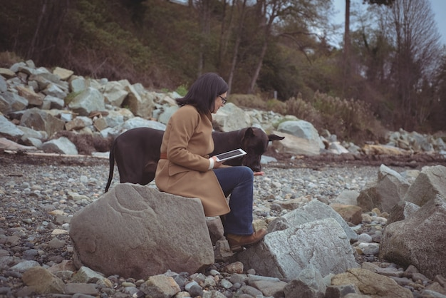 Femme tenant une tablette numérique par chien à la plage