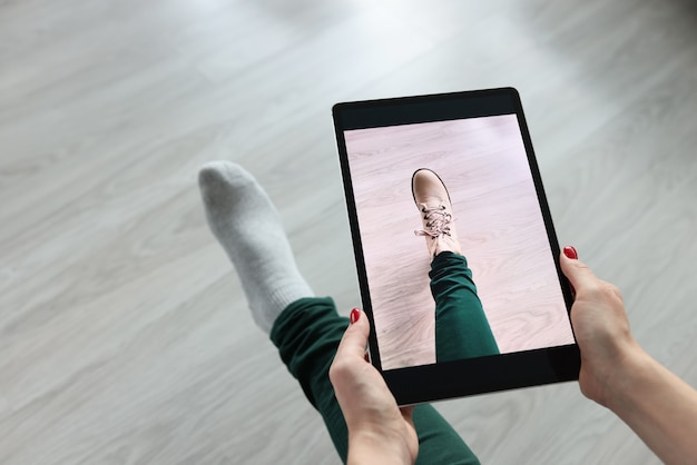Femme tenant la tablette sur sa jambe et essayant sur des chaussures agrandi. concept de vestiaire en ligne