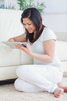 Femme tenant une tablette tactile devant un canapé