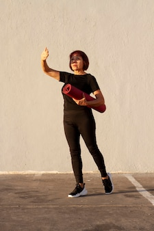 Femme tenant un tapis de fitness et couvre ses yeux du soleil