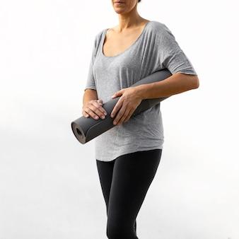 Femme tenant un tapis de yoga